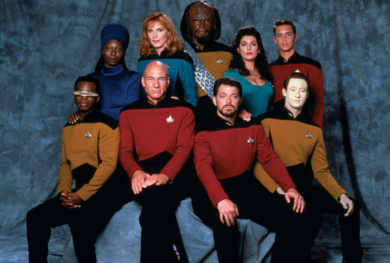 Ayaktakiler: Guinan, Dr. Beverly Crusher, Worf, Deanna Troi, Wesley Crusher. Oturanlar: Geordi La Forge, Jean Luc Picard, William Riker, Data.